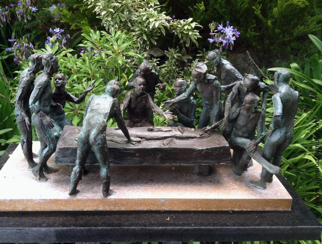 small bronze statue: men around a table